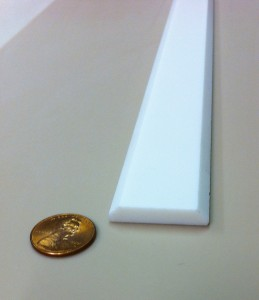 Batten strip, or turn around and use as corner molding, for covering seams.  Adhere to wall with silicone.